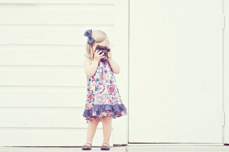 portrait of a little girl with vintage antique camera near a bar