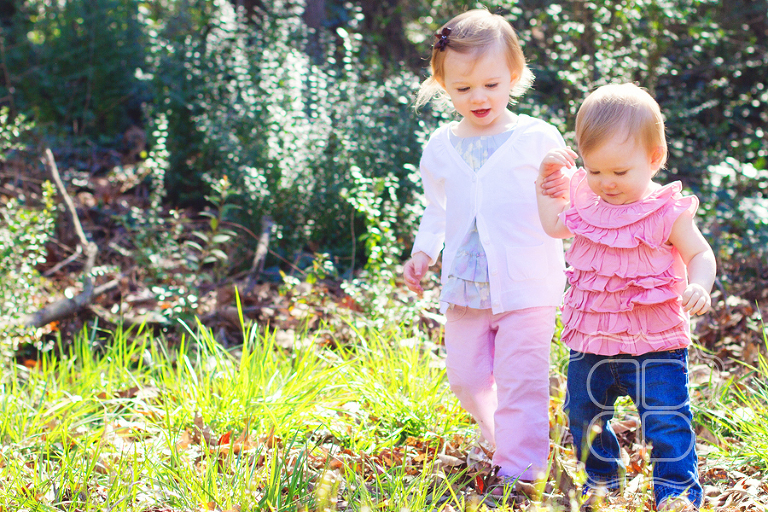 Big sister helps her little sister take a walk outside.