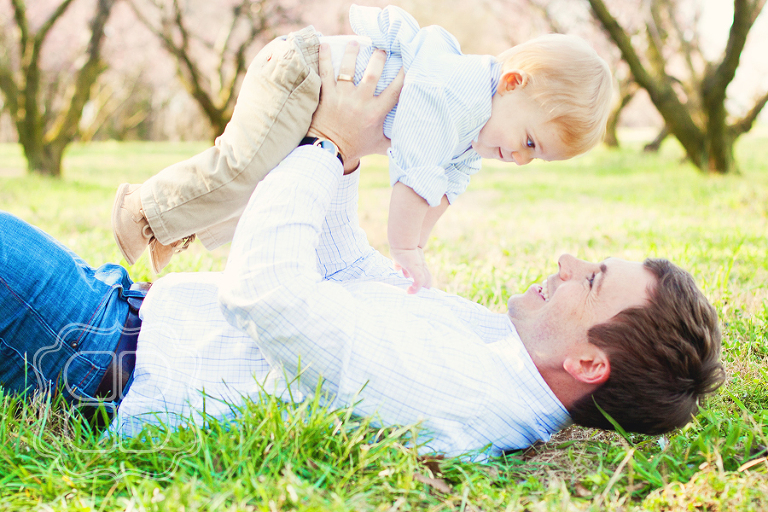 Baby and DAddy playfully pose for photographer