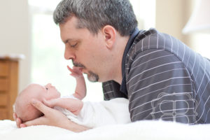 Newborn reaches for father's face