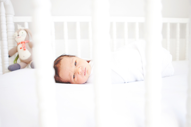 Newborn baby in his crib